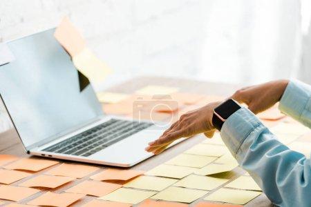 Photo pour Foyer sélectif de la femme gesticulant près d'un ordinateur portable avec écran vierge et des notes collantes - image libre de droit