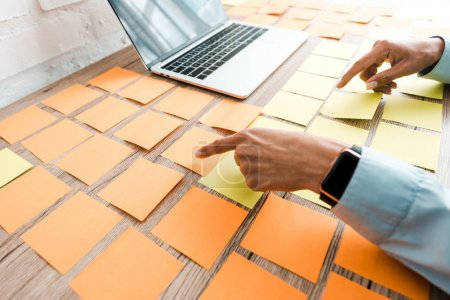 Photo for Cropped view of woman pointing with finger at sticky notes near laptop with blank screen - Royalty Free Image