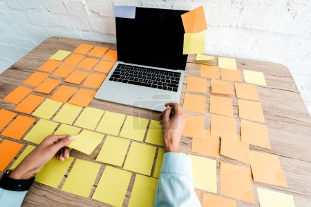 Photo for Cropped view of woman near sticky notes and laptop with blank screen on desk - Royalty Free Image
