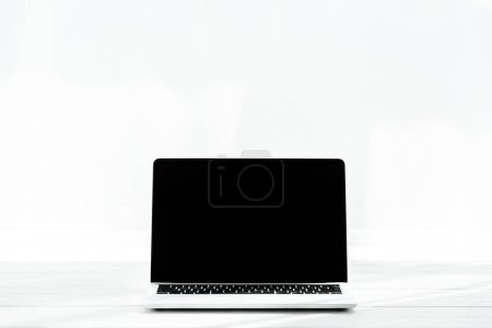 Photo for Laptop with blank screen on wooden table on white - Royalty Free Image