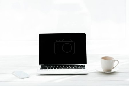 Photo pour Smartphone près de tasse de café et ordinateur portable avec écran blanc - image libre de droit