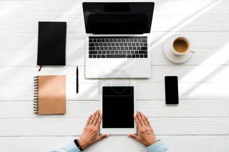 Photo pour Vue supérieure de la femme retenant la tablette numérique près des gadgets et de la tasse avec le café - image libre de droit