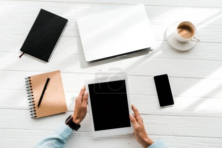 top view of woman holding digital tablet with blank screen near gadgets and cup with coffee