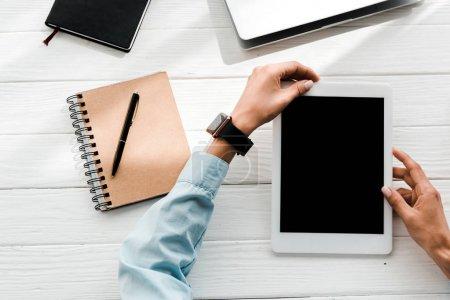 Photo pour Vue supérieure de la femme retenant la tablette numérique avec l'écran blanc près des cahiers - image libre de droit