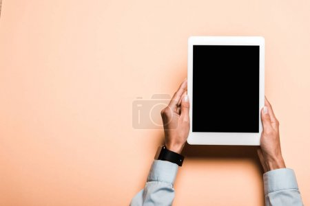 Photo for Cropped view of woman with smart watch on hand holding digital tablet with blank screen on pink - Royalty Free Image