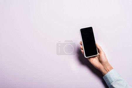 Photo pour Vue recadrée de femme retenant le smartphone avec l'écran blanc sur le pourpre - image libre de droit