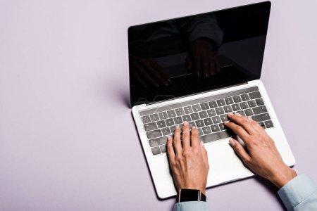 Photo pour Vue recadrée de la femme tapant sur ordinateur portable avec écran blanc sur violet - image libre de droit