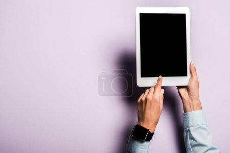cropped view of woman pointing with finger at digital tablet with blank screen on purple