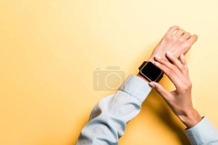 Photo pour Vue recadrée de la femme touchant montre intelligente avec écran blanc sur orange - image libre de droit