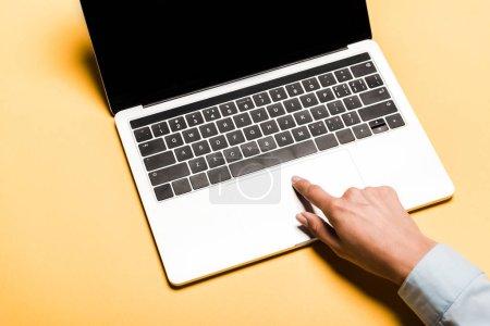 Photo pour Vue recadrée de la femme à l'aide d'un ordinateur portable avec écran blanc sur orange - image libre de droit