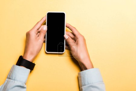 Photo for Cropped view of woman holding smartphone with blank screen on orange - Royalty Free Image