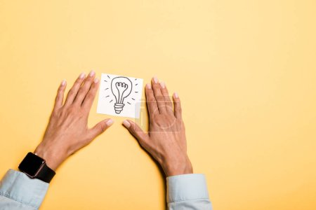 Photo for Top view of girl near card with drawn light bulb on orange - Royalty Free Image