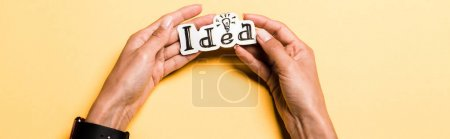 Photo for Panoramic shot of girl holding card with idea lettering on orange - Royalty Free Image