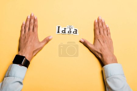 Photo for Top view of girl near card with idea lettering on orange - Royalty Free Image