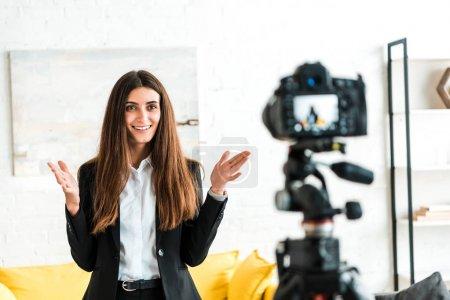 Photo pour Mise au point sélective de blogueur vidéo heureux gesticulant tout en regardant l'appareil photo numérique - image libre de droit