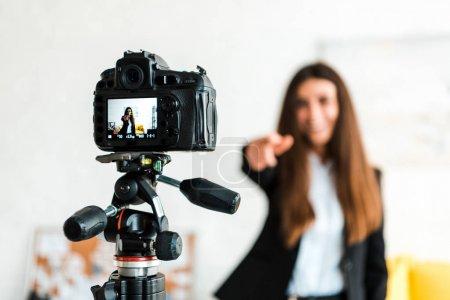 Photo pour Mise au point sélective de l'appareil photo numérique avec blogueur vidéo heureux gesticulant à l'écran - image libre de droit