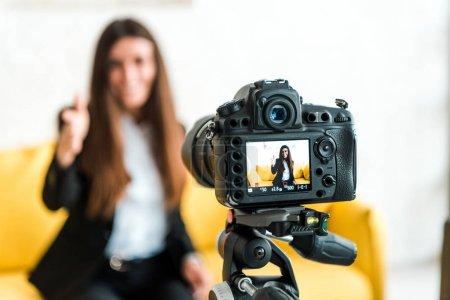 Foto de Enfoque selectivo de la cámara digital con blogger de vídeo feliz mostrando pulgar hacia arriba en la pantalla - Imagen libre de derechos