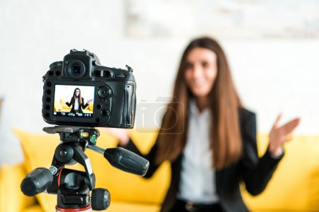 Photo pour Mise au point sélective de l'appareil photo numérique avec la fille heureuse faisant des gestes sur l'écran - image libre de droit