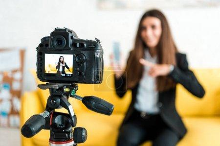 Photo pour Mise au point sélective de l'appareil photo numérique avec blogueur vidéo heureux pointant avec le doigt sur smartphone - image libre de droit