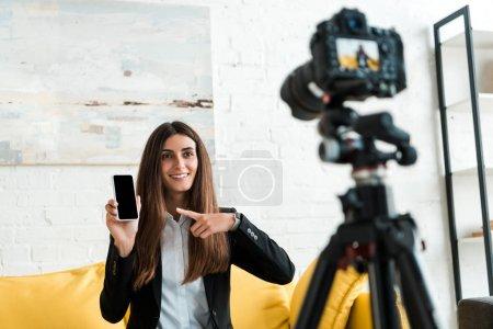Photo pour Mise au point sélective de blogueur vidéo heureux pointant avec le doigt au smartphone avec écran blanc près de l'appareil photo numérique - image libre de droit