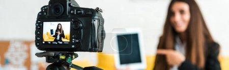 Photo pour Photo panoramique de l'appareil photo numérique avec blogueur vidéo heureux pointant avec le doigt à la tablette numérique avec écran blanc - image libre de droit