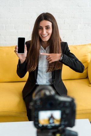 Photo pour Foyer sélectif de la femme heureuse pointant avec le doigt au smartphone avec l'écran blanc près de l'appareil-photo numérique - image libre de droit