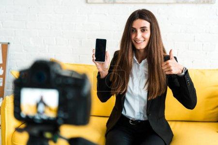 Photo pour Foyer sélectif de la femme heureuse affichant le pouce vers le haut et retenant le smartphone avec l'écran blanc près de l'appareil-photo numérique - image libre de droit