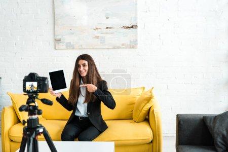 Photo pour Mise au point sélective de blogueur vidéo heureux pointant du doigt à la tablette numérique avec écran blanc près de l'appareil photo numérique - image libre de droit