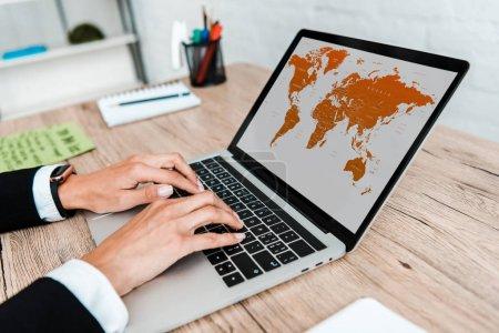 Photo pour Foyer sélectif de la femme d'affaires tapant sur l'ordinateur portatif avec la carte à l'écran - image libre de droit