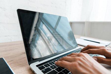 Photo pour Vue recadrée de femme tapant sur le clavier d'ordinateur portatif dans le bureau - image libre de droit
