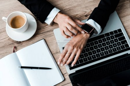 vista superior de la mujer tocando reloj inteligente cerca del ordenador portátil y la taza de café