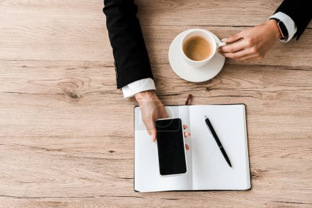 Photo for Top view of businesswoman holding smartphone with blank screen and cup with coffee near notebook with pen - Royalty Free Image