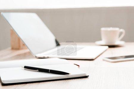 Foto de Enfoque selectivo de cuaderno y pluma cerca de gadgets en la mesa - Imagen libre de derechos