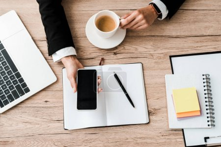 Photo pour Vue supérieure de femme d'affaires retenant le smartphone avec l'écran blanc et la tasse avec le café près du cahier et du stylo - image libre de droit