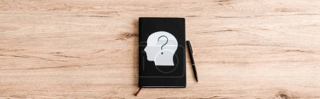 Photo pour Tir panoramique de la tête humaine de papier avec le point d'interrogation sur le cahier noir près du stylo - image libre de droit