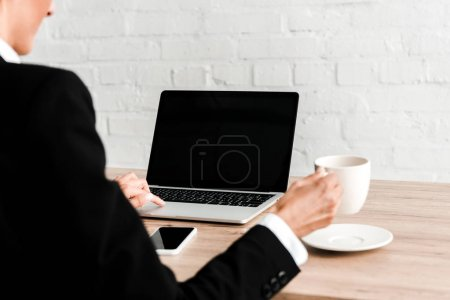 Photo for Selective focus of woman holding cup while sitting near gadgets in office - Royalty Free Image