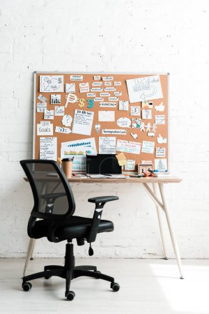 Photo for Notice board with lettering on sticky notes near table and chair - Royalty Free Image