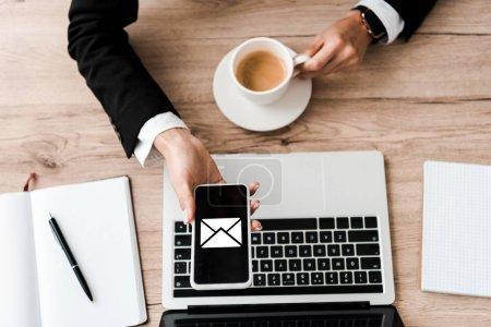 Photo pour Vue du dessus de la femme d'affaires tenant smartphone avec enveloppe à l'écran et tasse avec café près de l'ordinateur portable - image libre de droit