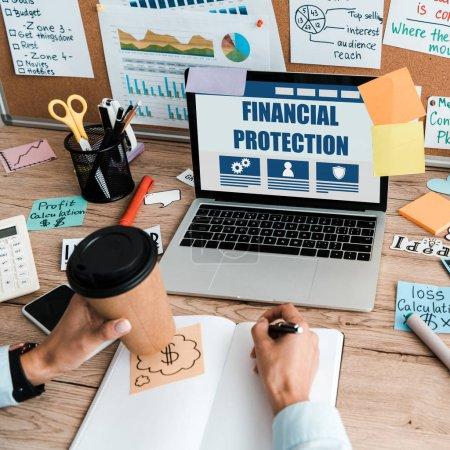 Photo pour Vue recadrée de femme d'affaires avec le stylo et la tasse en papier près de l'ordinateur portatif avec la protection financière sur l'écran - image libre de droit