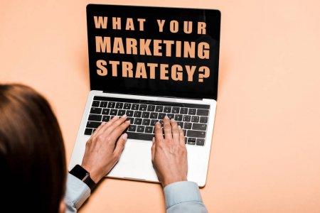 Photo pour Vue recadrée de la femme tapant sur l'ordinateur portatif avec ce que votre lettre de stratégie de marketing sur le rose - image libre de droit