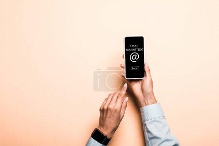 Photo pour Vue recadrée de la femme pointant du doigt le smartphone avec lettrage marketing par e-mail sur rose - image libre de droit