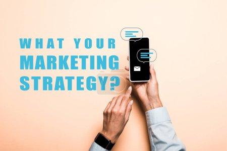 Foto de Vista recortada de la mujer señalando con el dedo en el teléfono inteligente con lo que su estrategia de marketing letras en rosa - Imagen libre de derechos