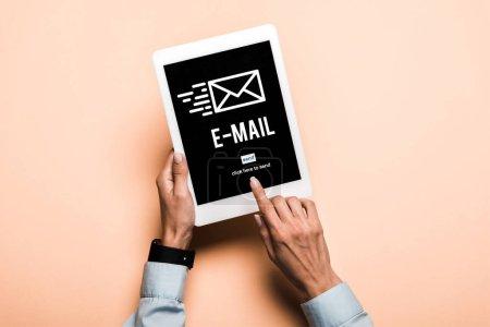 Photo pour Vue recadrée de femme pointant avec le doigt à la tablette numérique avec le lettrage d'email sur le rose - image libre de droit