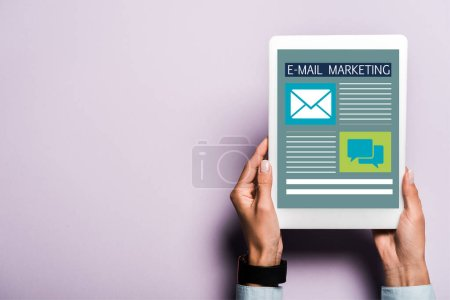 cropped view of woman holding digital tablet with email marketing lettering on purple