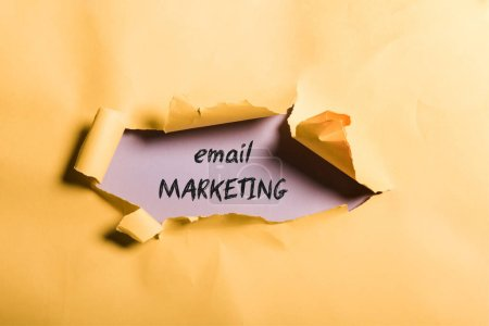 Photo pour Papier orange en lambeaux avec lettrage email marketing et bords roulés sur violet - image libre de droit