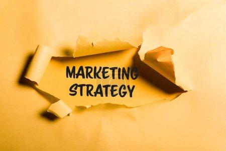 Photo pour Papier en lambeaux avec lettrage de stratégie de marketing et bords roulés sur orange - image libre de droit