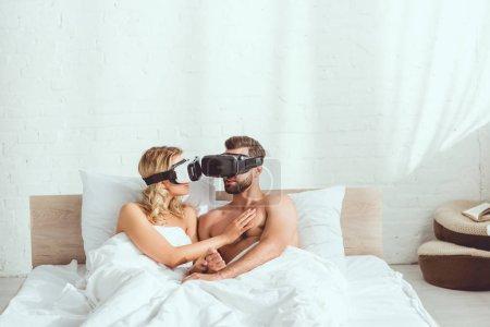 junges Paar umarmt sich im Bett und benutzt Virtual-Reality-Headsets