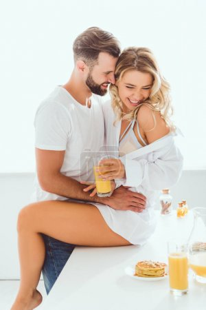 Photo for Smiling man hugging girlfriend sitting on kitchen table and holding glass of orange juice - Royalty Free Image
