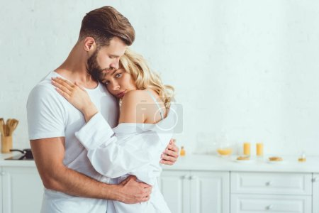 Photo for Beautiful young woman looking at camera while embracing with boyfriend in kitchen - Royalty Free Image