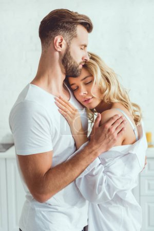 Photo for Handsome man embracing young beautiful girlfriend in kitchen - Royalty Free Image